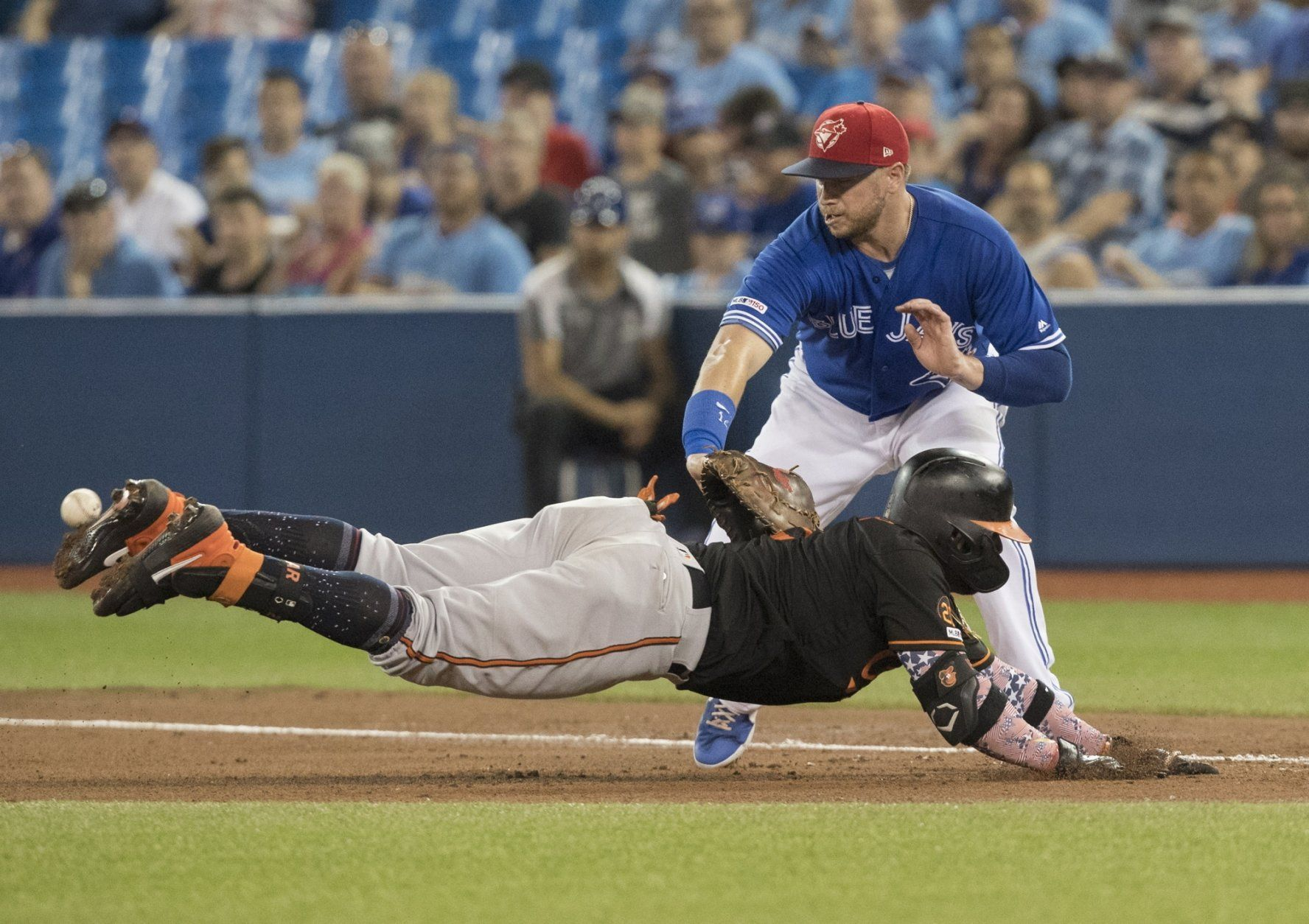 Baltimore Orioles' Jonathan Villar dives back to first but Toronto Blue Jays' Justin Smoak can not get a handle on a throw to him, allowing Villar to advance to second base during the fifth inning of a baseball game Friday, July 5, 2019, in Toronto. (Fred Thornhill/The Canadian Press via AP)