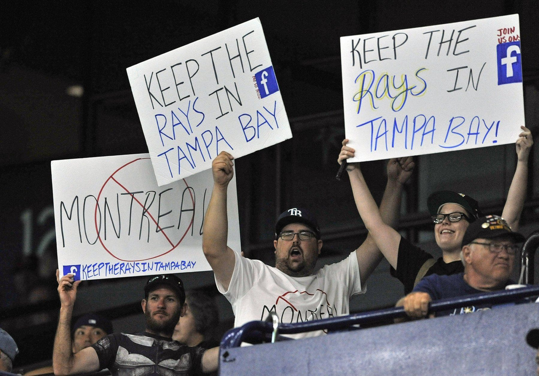A group of Tampa Bay Rays fans carry signs around the stadium during a baseball game against the Baltimore Orioles Monday, July 1, 2019, in St. Petersburg, Fla. (AP Photo/Steve Nesius)