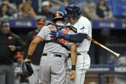 Tampa Bay Rays' Avisail Garcia, right, holds up Baltimore Orioles catcher Pedro Severino, left, after Severino was hit by a foul ball into his shoulder during the third inning of a baseball game Monday, July 1, 2019, in St. Petersburg, Fla. (AP Photo/Steve Nesius)