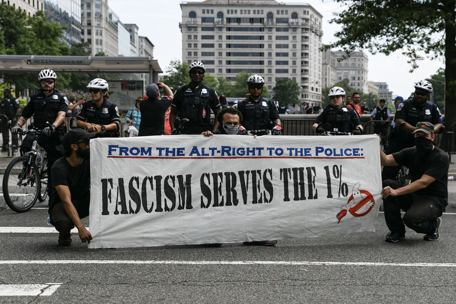 Antifa protesters pose with a sign in front of Washington, D.C. police officers, as members of the far-right rally against conservative censorship in social media. Trump supporters and anti-fascist organizers held dueling rallies across the street from each other, leading to high tensions as D.C. and U.S. Park Police largely held the peace. (WTOP/Alejandro Alvarez)