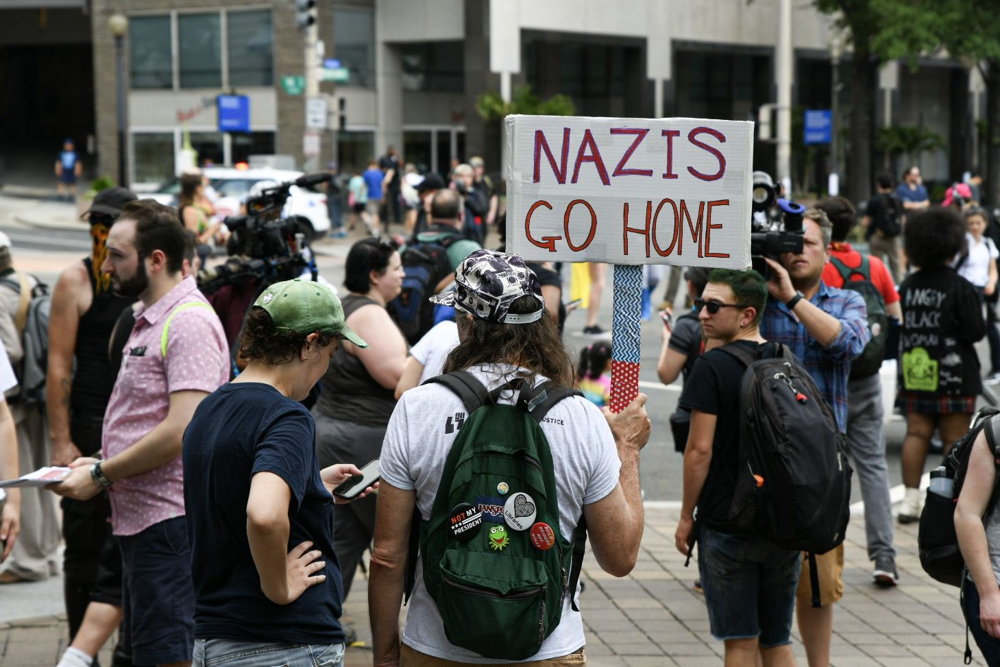 A protester opposing the far-right holds a sign against white supremacy in a counter-protest to a July 6, 2019 rally by far-right figures in Washington, D.C.'s Freedom Plaza. Trump supporters and anti-fascist organizers held dueling rallies across the street from each other, leading to high tensions as D.C. and U.S. Park Police largely held the peace. (WTOP/Alejandro Alvarez)