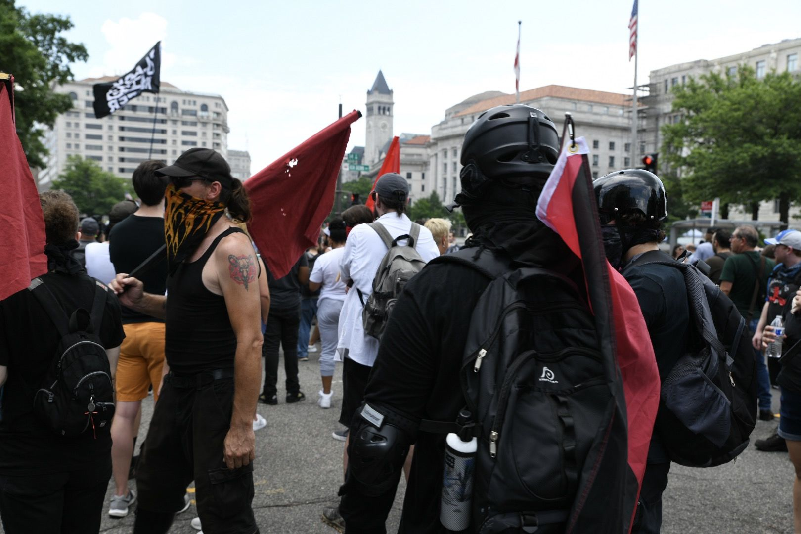 Far-left activists known as antifa wear helmets and dress in all black as they patrol Washington, D.C.'s 14th Street to confront supporters of President Donald Trump on July 6, 2019. Trump supporters and anti-fascist organizers held dueling rallies across the street from each other, leading to high tensions as D.C. and U.S. Park Police largely held the peace. (WTOP/Alejandro Alvarez)