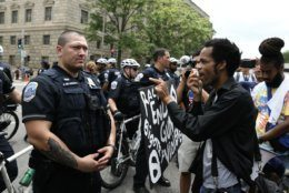 A protester confronts a Washington, D.C. police officer, accusing them of protecting white supremacists, while opposing a far-right rally on July 6, 2019. Trump supporters and anti-fascist organizers held dueling rallies across the street from each other, leading to high tensions as D.C. and U.S. Park Police largely held the peace. (WTOP/Alejandro Alvarez)