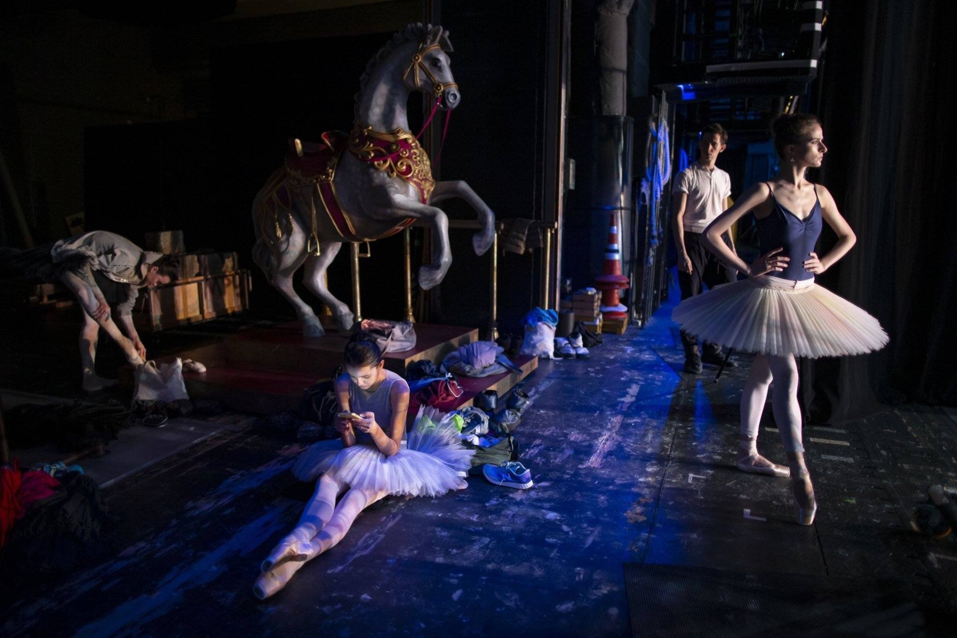In this photo taken on Tuesday, June 11, 2019, a ballerina looks at her smartphone as others prepare for a performance during a rehearsal in the Bolshoi Theater in Moscow, Russia. Backstage, the dancers warm up, chalk their ballet shoes, or sit checking their social media, but once onstage, the ballet director at the Bolshoi Makhar Vaziev is an exacting ballet master who scrutinizes technique closely and spares no one's feelings if he sees a mistake.  (AP Photo/Alexander Zemlianichenko)