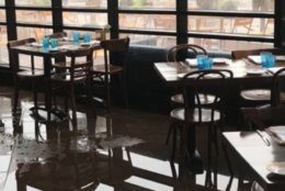 Water pooling on the floor of a restaurant reflects tables and chairs.