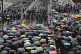 In this July 1, 2019, photo, protesters holding umbrellas face off police officers in anti-riot gear in Hong Kong. Protesters in Hong Kong pushed barriers and dumpsters into the streets early Monday morning in an apparent bid to block access to a symbolically important ceremony marking the anniversary of the return of the former British colony to China. (AP Photo/Kin Cheung, File)