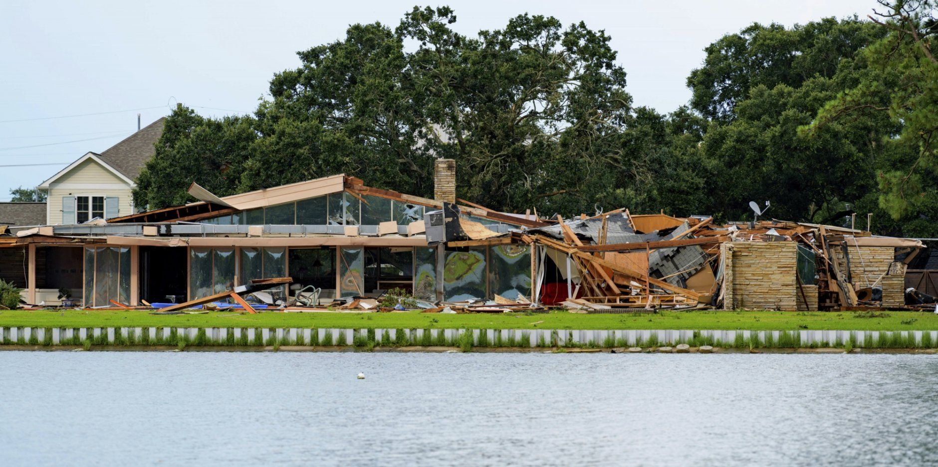 This photo shows the damaged home of Eric and Indra Ehlenberger in New Orleans on Wednesday, July 10, 2019, following a storm that went through the area. The storm swamped New Orleans streets and paralyzed traffic Wednesday as concerns grew that even worse weather was on the way: a possible hurricane that could strike the Gulf Coast and raise the Mississippi River to the brim of the city's protective levees. (AP Photo/Matthew Hinton)