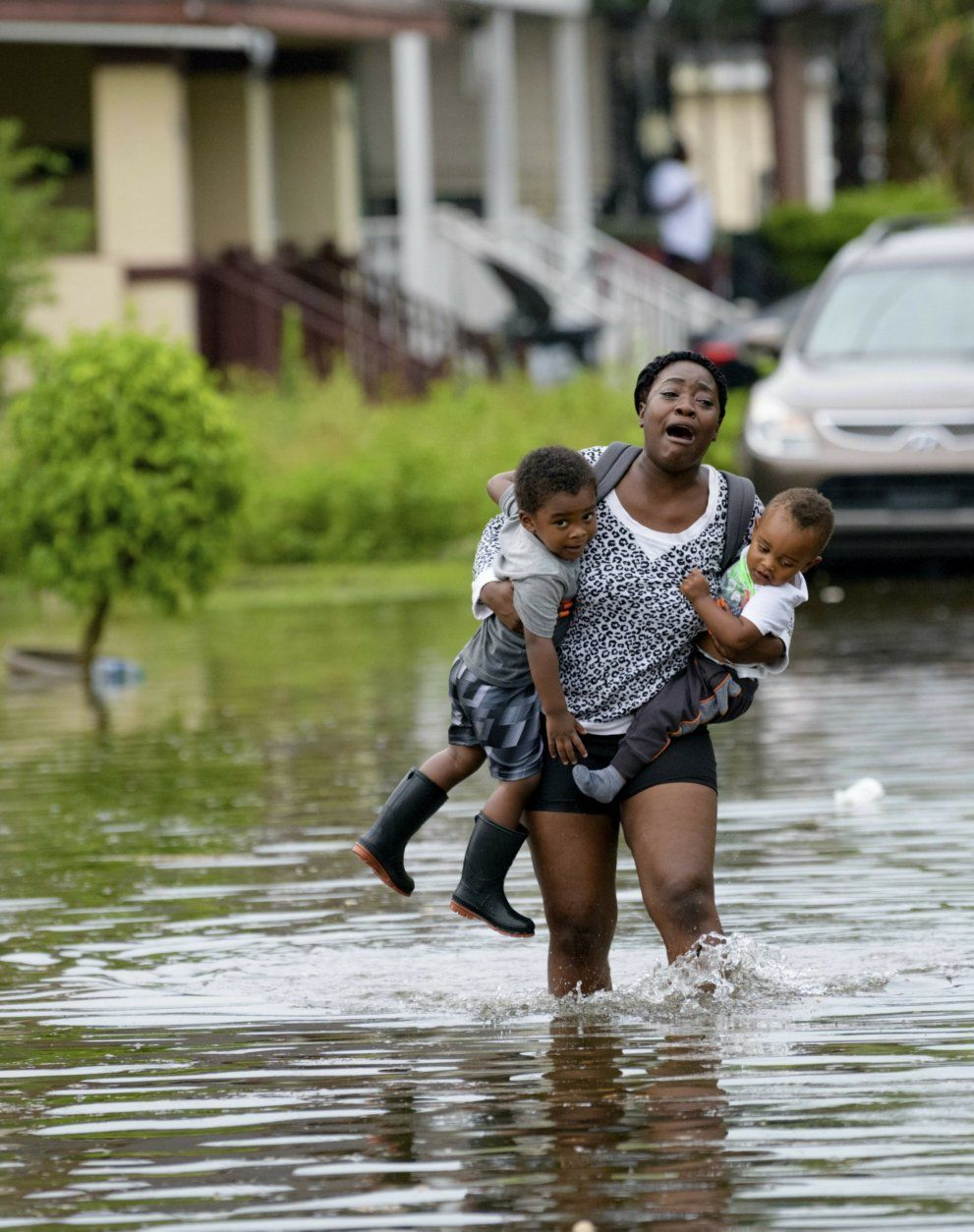 Terrian Jones reacts as she feels something moving in the water at her feet as she carries Drew and Chance Furlough to their mother on Belfast Street near Eagle Street in New Orleans after flooding from a storm dumped lots of rain on Wednesday, July 10, 2019.  (AP Photo/Matthew Hinton)