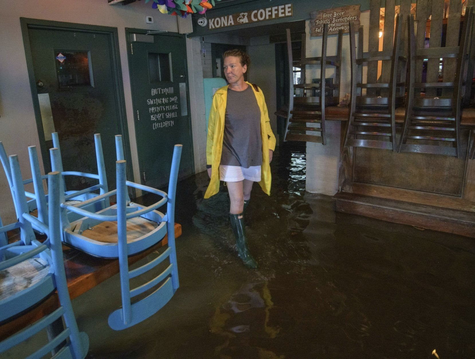Aimee Cutter the owner of Beach House restaurant walks through water surge from Lake Pontchartrain on Lakeshore Drive in Mandeville, La., ahead of Tropical Storm Barry, Saturday, July 13, 2019.  Barry is expected to reach hurricane strength by the time its center reaches the Louisiana coast, expected before noon local time. The storm is expected to weaken after it moves inland.  (AP Photo/Matthew Hinton)