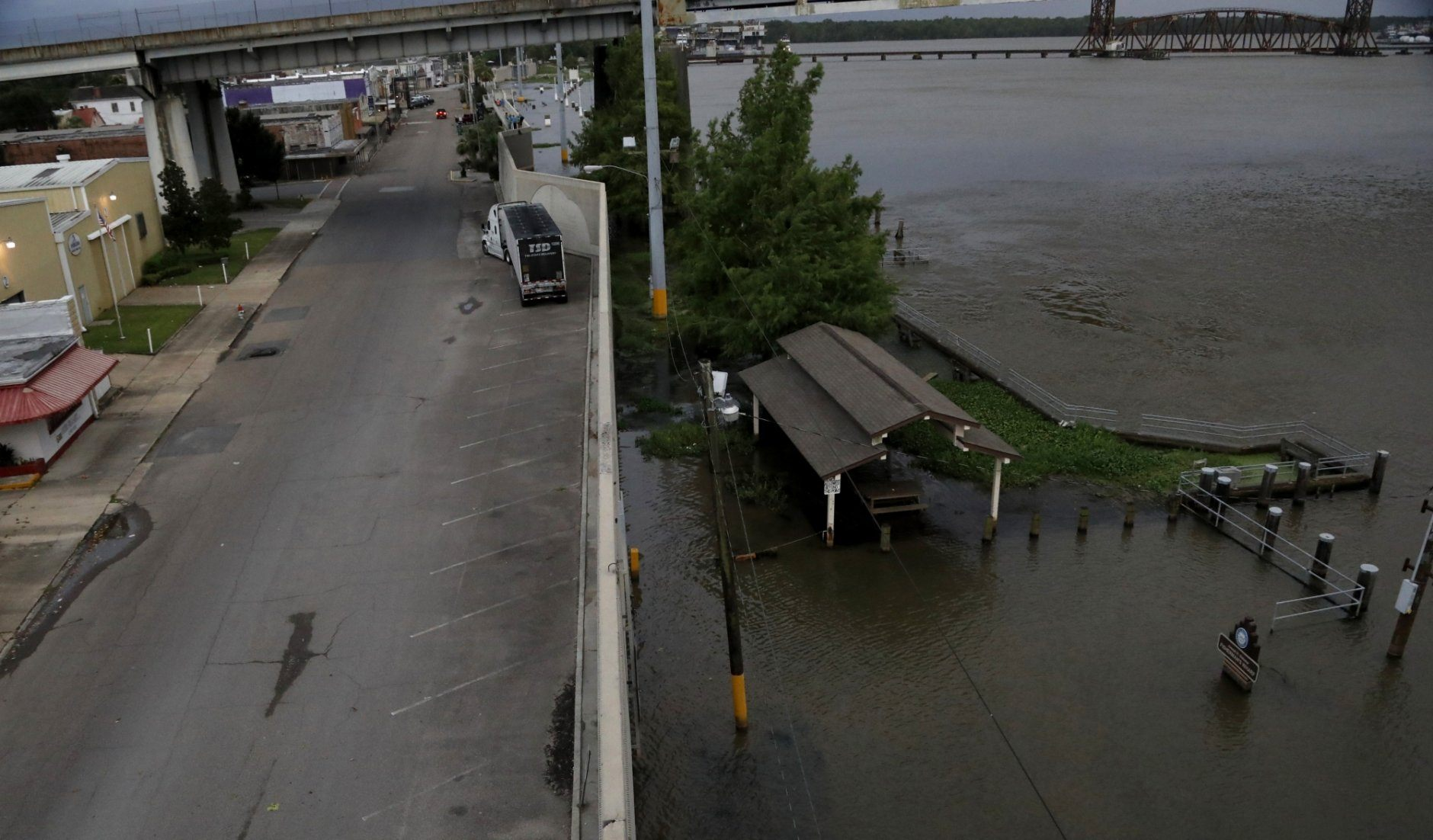 The flood wall near the Long-Allen Bridge in Morgan City, La., continues to protect residents and area businesses as the waters rise in the Atchafalaya River, Friday, July 12, 2019. With Tropical Storm Barry expected to blow ashore early Saturday near Morgan City as the first hurricane of the season, authorities rushed to close floodgates and raise the barriers around the New Orleans metropolitan area of 1.3 million people for fear of disastrous flooding.. (AP Photo/Rogelio V. Solis)