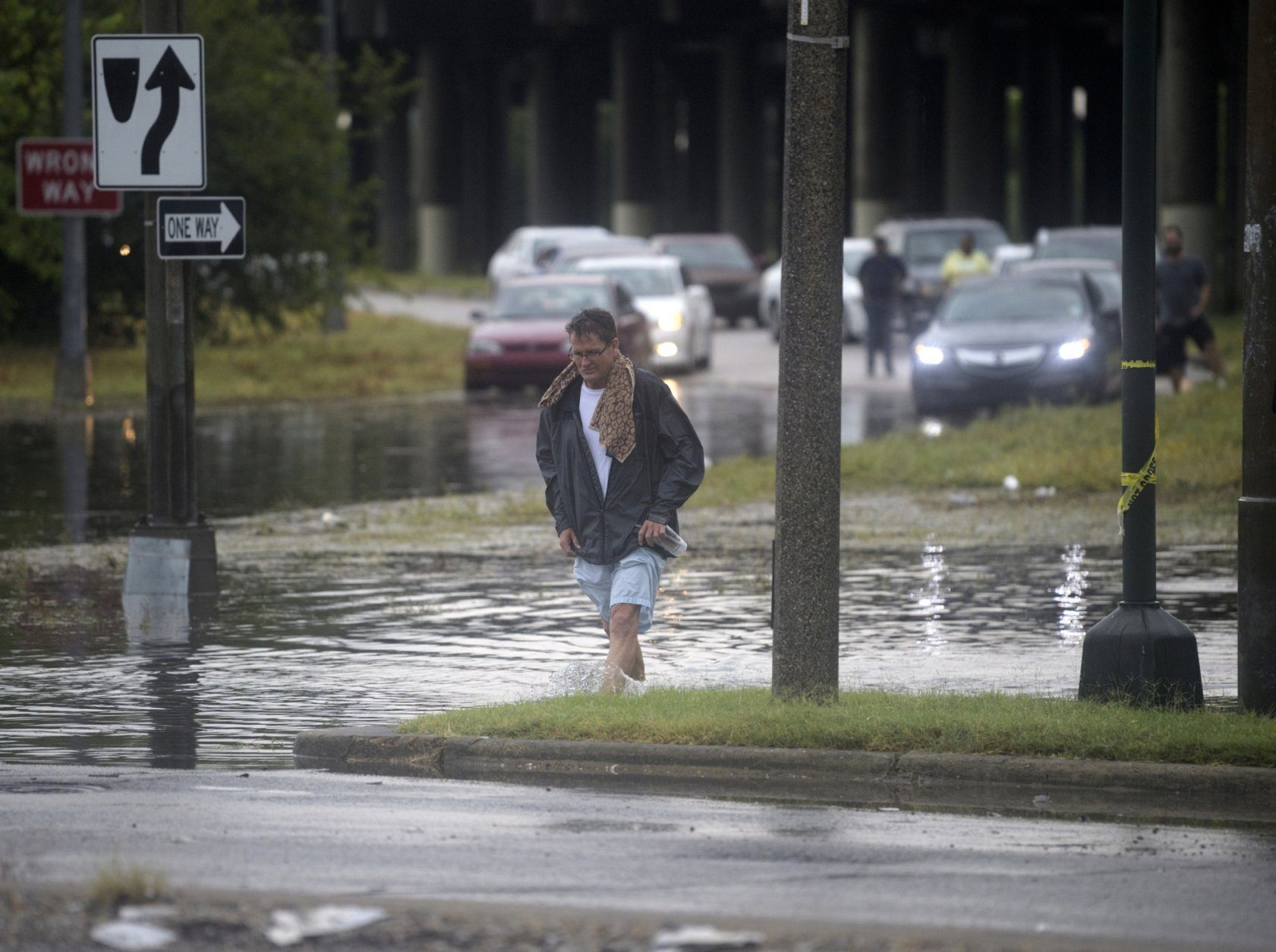 A man walks through standing water at the intersection at Franklin Ave. and 610 in New Orleans after a severe thunderstorm caused street flooding Wednesday, July 10, 2019.  (Max Becherer/The Advocate via AP)