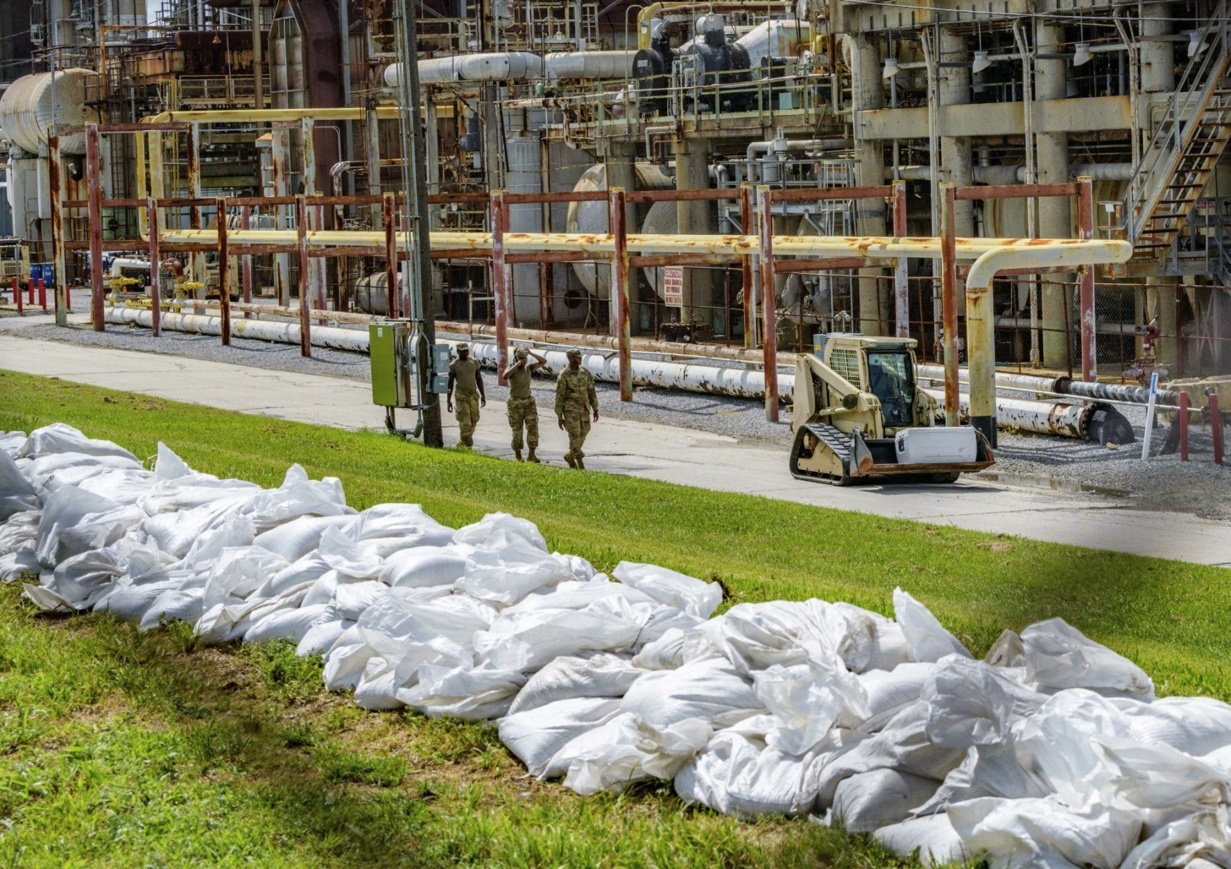 FILE - In this Thursday, July 11, 2019, file photo, soldiers with the U.S. Army National Guard work on adding sandbags to levees by the Chalmette Refining plant in Chalmette, La., ahead of Tropical Storm Barry. Barry could harm the Gulf Coast environment in a number of ways. But scientists say it's hard to predict how severe the damage will be. (AP Photo/Matthew Hinton, File)
