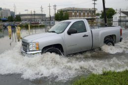 A truck passes by the University Medical Center (UMC) with the Mercedes-Benz Superdome in the background on Glavez Street in New Orleans after flooding from a storm Wednesday, July 10, 2019. Louisiana Gov. John Bel Edwards has declared a state of emergency in anticipation of tropical weather that could dump as much as 15 inches (38 centimeters) of rain in the state over the coming days. (AP Photo/Matthew Hinton)