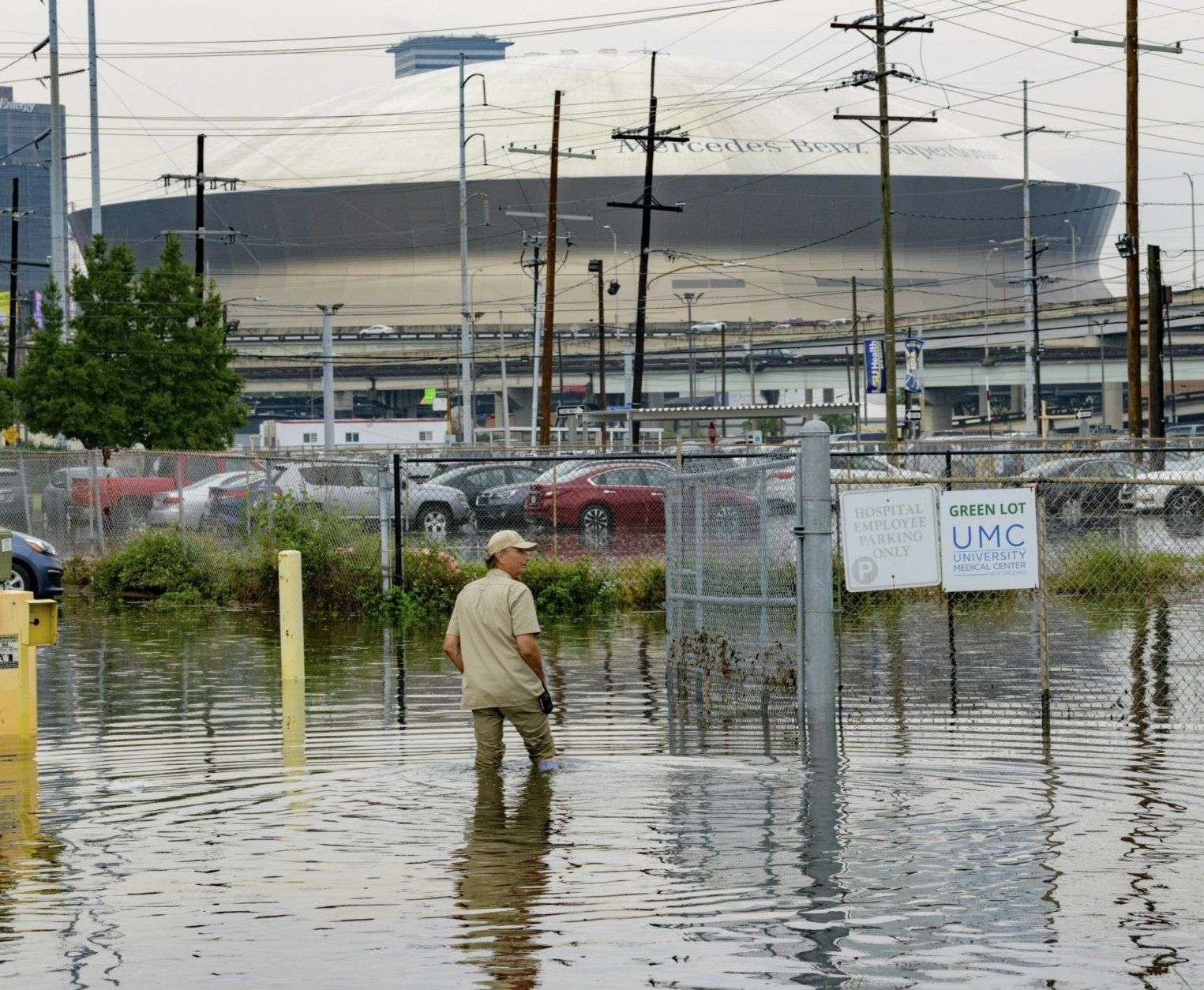 Frank Conforto Jr. walks in the parking lot of the University Medical Center (UMC) with the Mercedes-Benz Superdome in the background on Glavez Street in New Orleans after flooding from a storm Wednesday, July 10, 2019. Louisiana Gov. John Bel Edwards has declared a state of emergency in anticipation of tropical weather that could dump as much as 15 inches (38 centimeters) of rain in the state over the coming days. (AP Photo/Matthew Hinton)