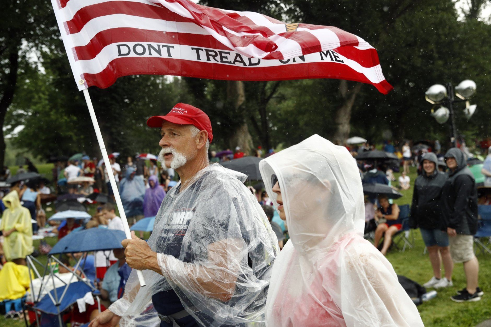 Supporters of President Donald Trump who did not wish to provide their names, walk on the National Mall in Washington as rain falls before Independence Day celebrations, Thursday, July 4, 2019. (AP Photo/Patrick Semansky)