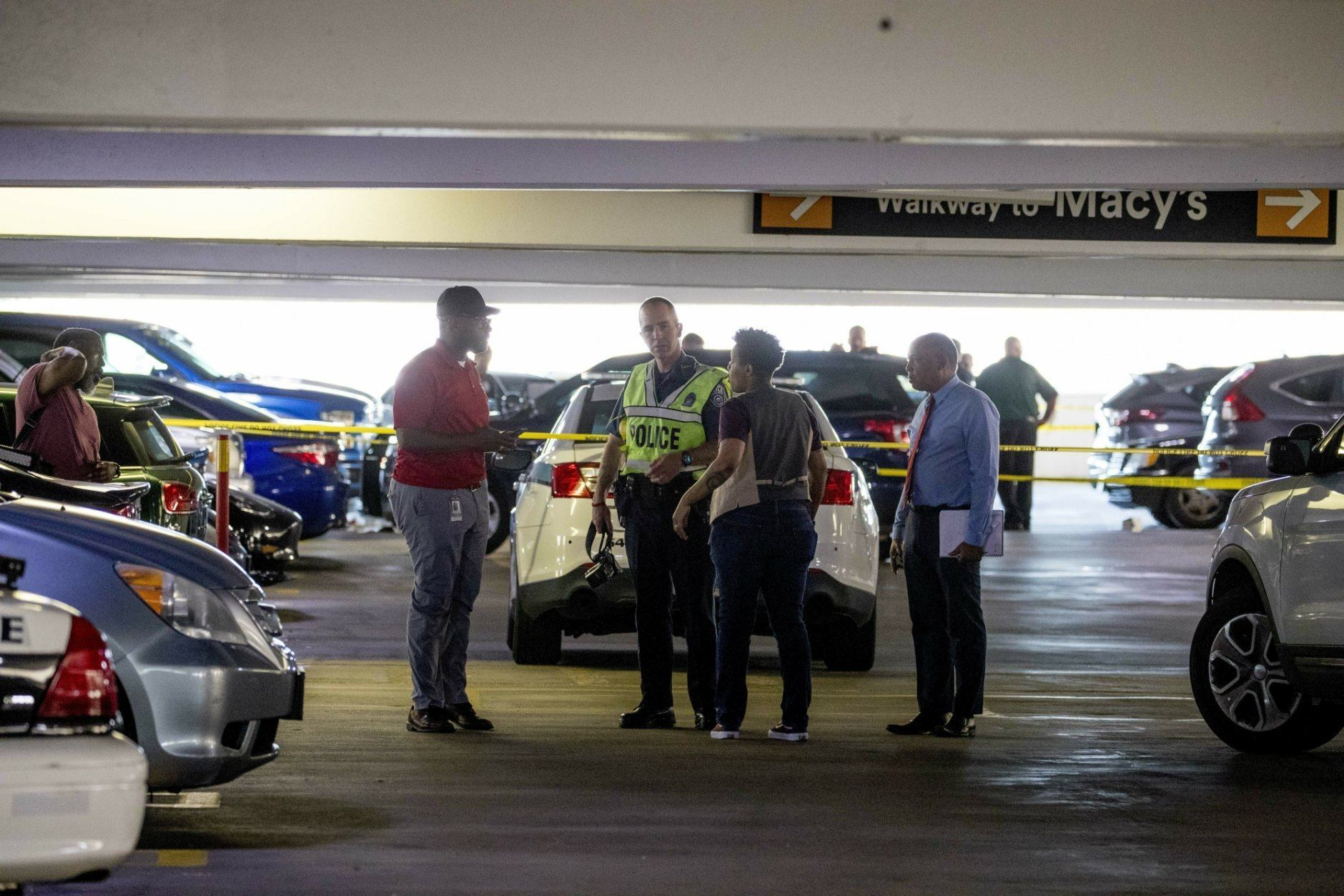 Police officers stand at a crime scene following a shooting at the parking garage for the Fashion Centre at Pentagon City, also known as Pentagon City Mall, Monday, July 1, 2019, in Arlington. (AP Photo/Andrew Harnik)