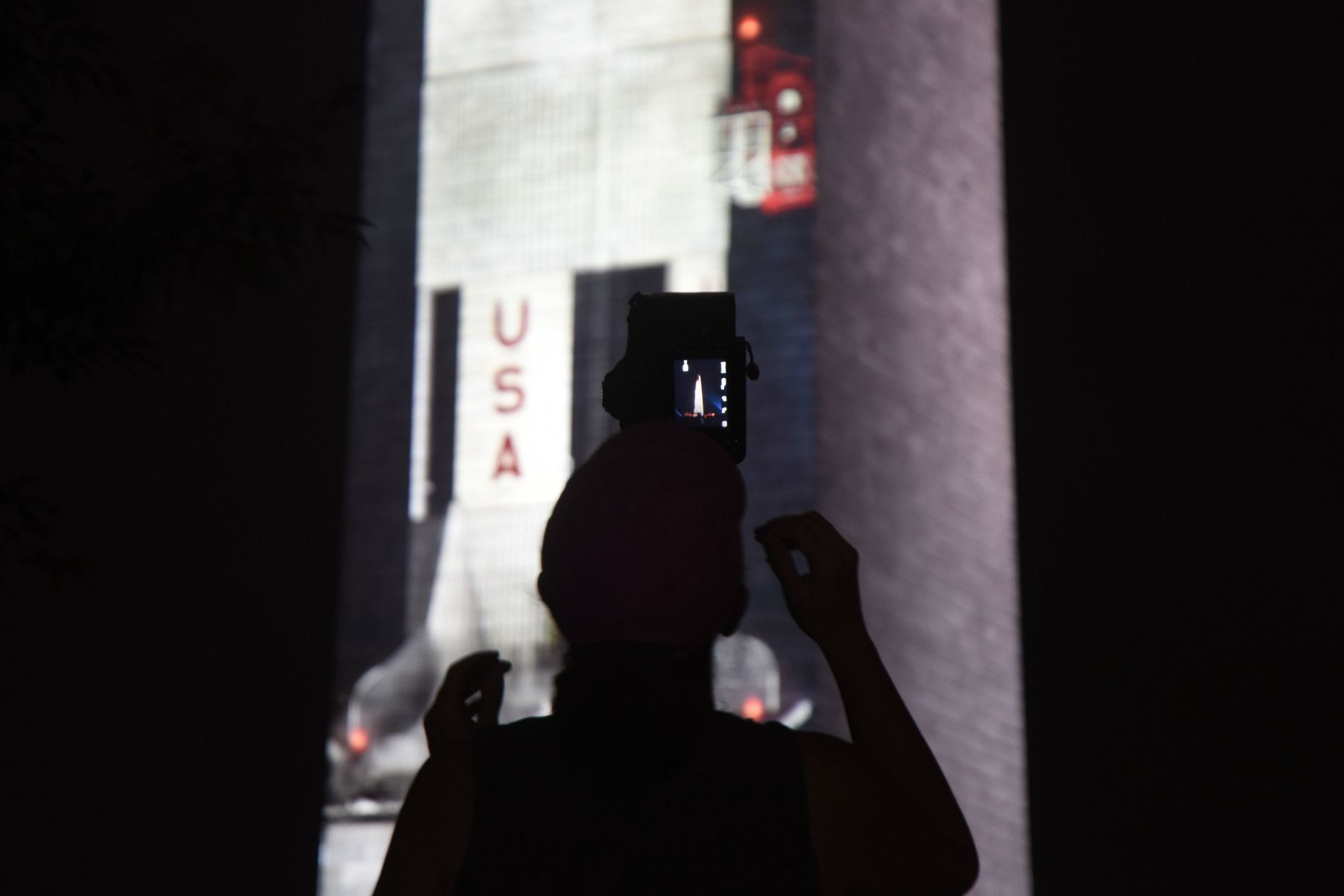 A projection of a 363-foot Saturn V rocket projected on the Washington Monument