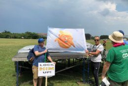 An inflatable image of President Donald Trump as a baby has been deflated, so protesters are using a flag image of it instead. (WTOP/Mike Murillo)