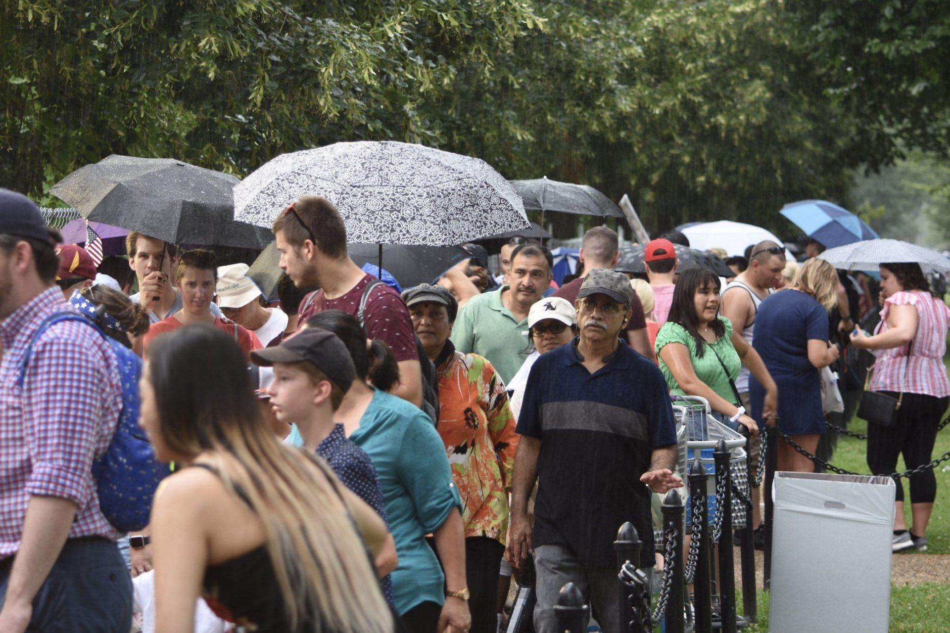 Umbrellas come out at the 20th Street/Constitution Avenue checkpoint near the National Mall on Thursday, July 4, 2019. (WTOP/Dave Dildine)