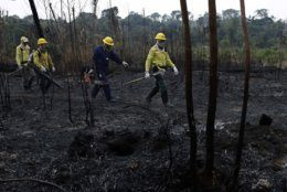 Firefighters walk across charred land to another area as they work to put out fires along the road to Jacunda National Forest in the Vila Nova Samuel region, near the city of Porto Velho in Rondonia state, part of Brazil's Amazon, Sunday, Aug. 25, 2019. Leaders of the Group of Seven nations said Sunday they were preparing to help Brazil fight the fires burning across the Amazon rainforest and repair the damage even as tens of thousands of soldiers were being deployed to fight the blazes that have caused global alarm. (AP Photo/Eraldo Peres)