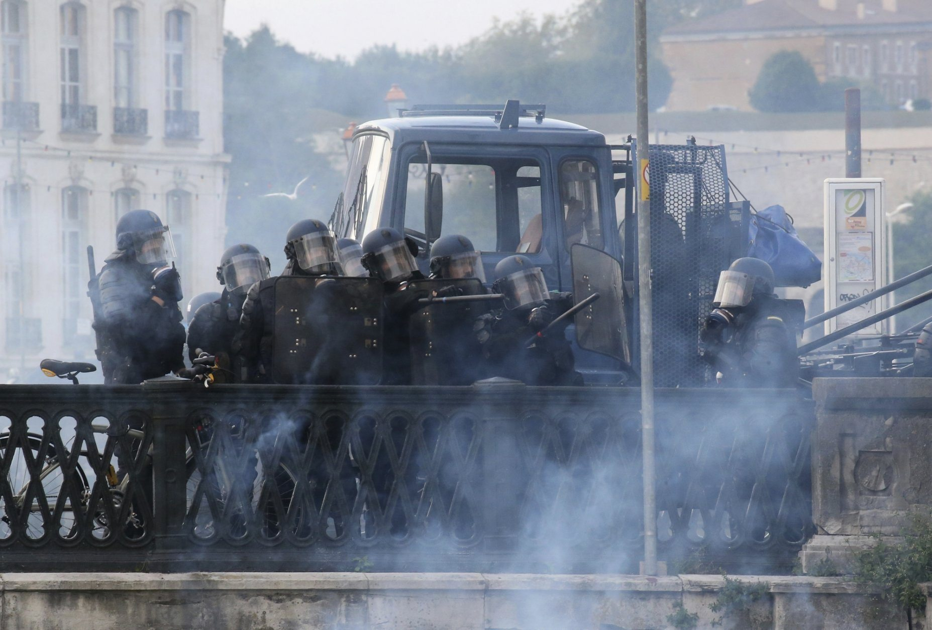 Police fire gather behind their shields as they clash with protestors in Bayonne, France, Saturday, Aug. 24, 2019. World leaders and protesters are converging on the southern French resort town of Biarritz for the G-7 summit. Police have fired water cannon at about 400 anti-capitalist protesters blocking roads in a town near the venue of the G-7 summit. A few protesters threw rocks at police but the crowd in Bayonne was largely peaceful. (AP Photo/Bob Edme)