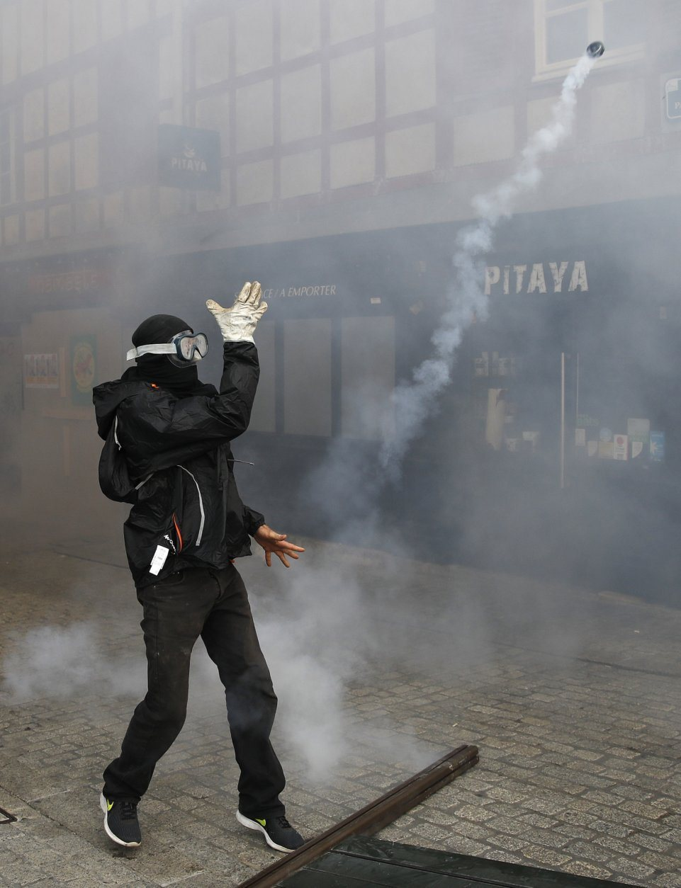 A protestor throws away a teargas canister fired by police in Bayonne, France, Saturday, Aug. 24, 2019. World leaders and protesters are converging on the southern French resort town of Biarritz for the G-7 summit. Police have fired water cannon at about 400 anti-capitalist protesters blocking roads in a town near the venue of the G-7 summit. A few protesters threw rocks at police but the crowd in Bayonne was largely peaceful. (AP Photo/Emilio Morenatti)