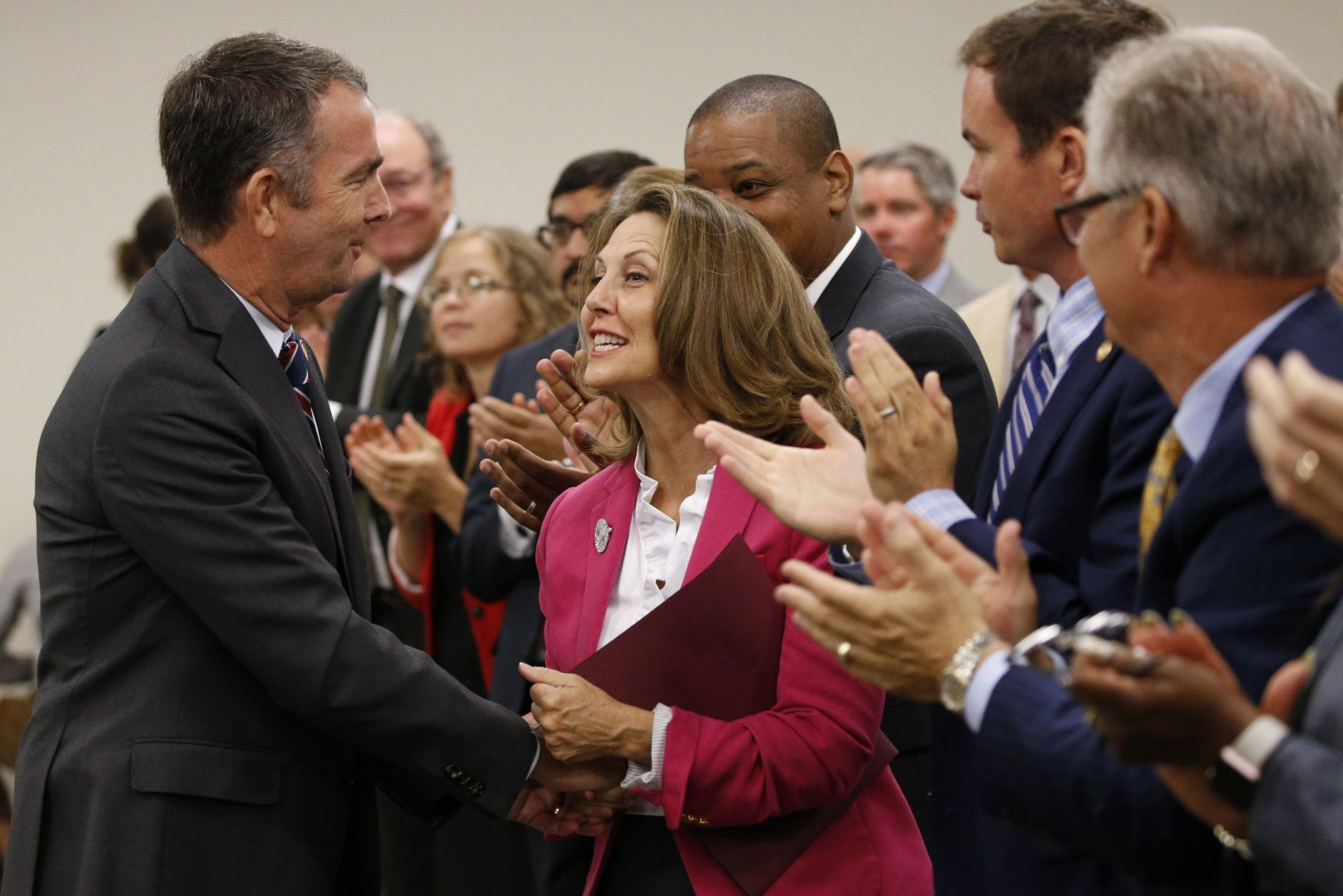 Virginia Gov. Ralph Northam, left, greets his wife, Pam, after delivering his budget update before a joint meeting of the House and Senate money committees at the Capitol in Richmond, Va., Tuesday, Aug. 20, 2019. (AP Photo/Steve Helber)