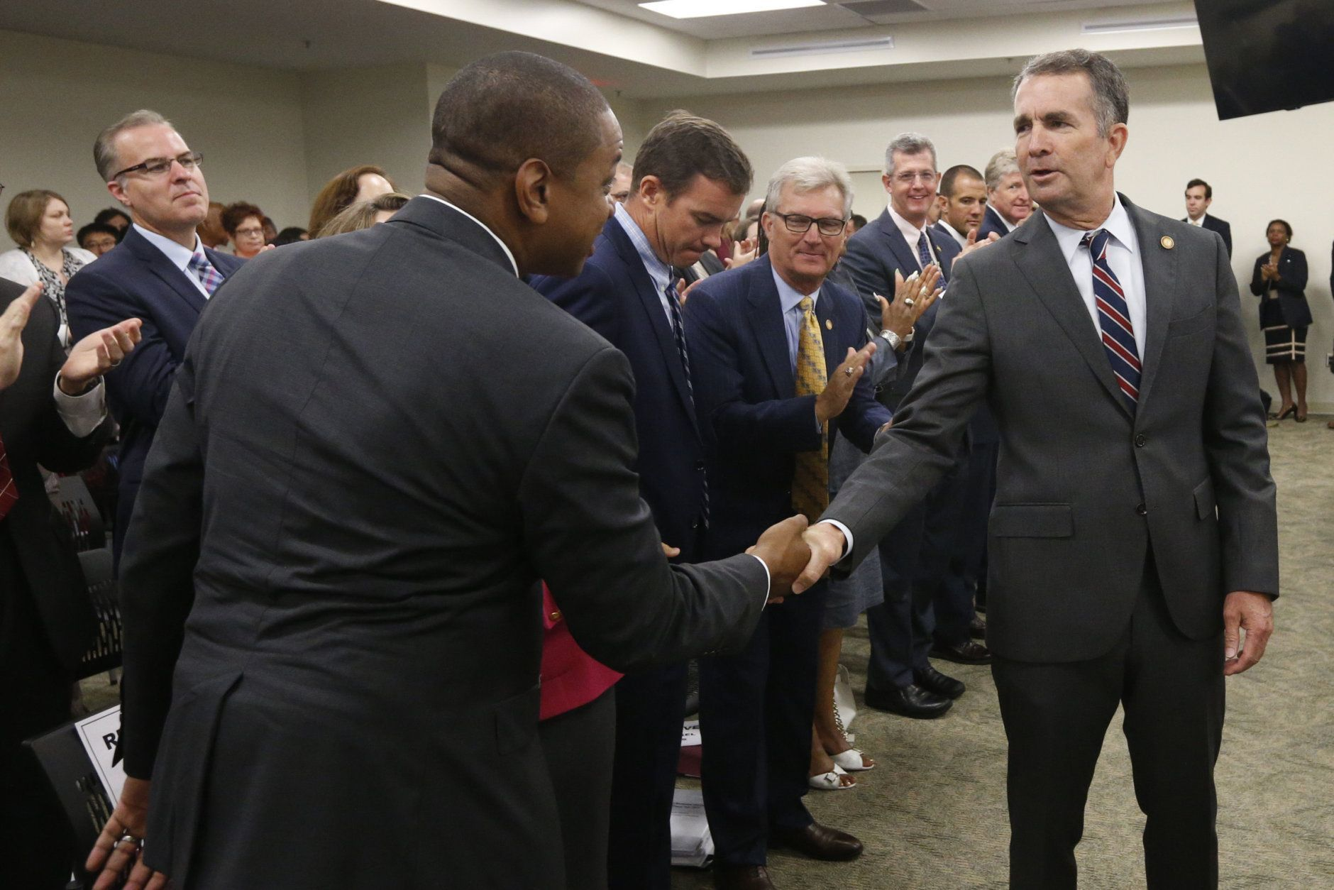 Virginia Gov. Ralph Northam, right, greets Lt. Gov. Justin Fairfax, left, as he prepares to deliver his budget update before a joint meeting of the House and Senate money committees at the Capitol in Richmond, Va., Tuesday, Aug. 20, 2019. (AP Photo/Steve Helber)