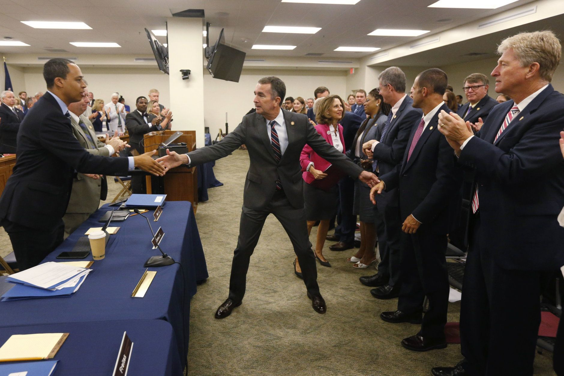 Virginia Gov. Ralph Northam greets legislators and staff after he delivered his budget update before a joint meeting of the House and Senate money committees at the Capitol in Richmond, Va., Tuesday, Aug. 20, 2019. (AP Photo/Steve Helber)