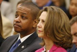 Virginia Lt. Gov. Justin Fairfax, left, listens along with Virginia First Lady Pam Northam, right as Virginia Gov. Ralph Northam delivers his budget update before a joint meeting of the House and Senate money committees at the Capitol in Richmond, Va., Tuesday, Aug. 20, 2019. (AP Photo/Steve Helber)