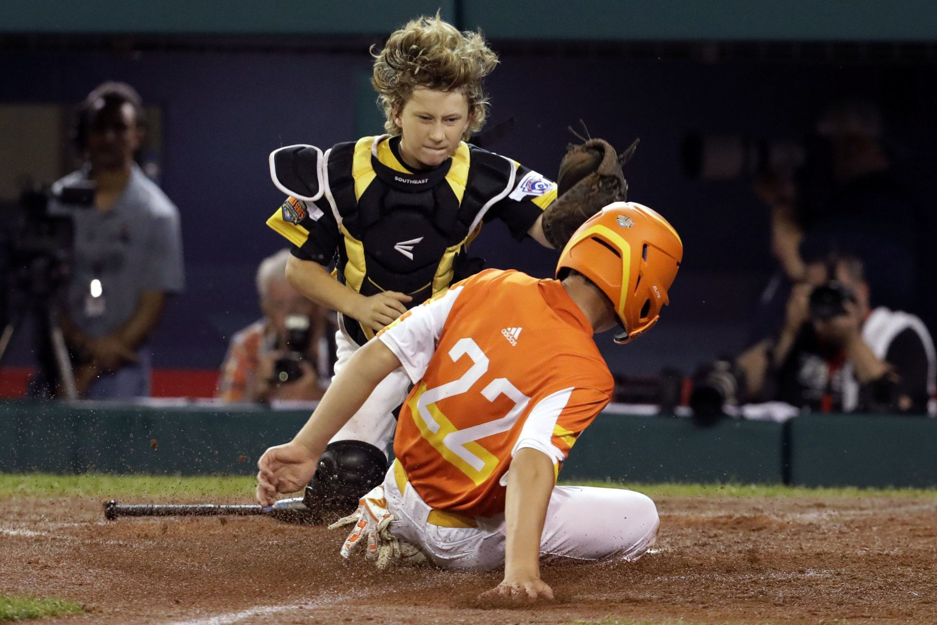 River Ridge, La.'s Reece Roussel (22) scores ahead of the tag by South Riding, Va.'s Noah Culpepper during the third inning of a baseball game at the Little League World Series in South Williamsport, Pa., Thursday, Aug. 22, 2019. (AP Photo/Gene J. Puskar)