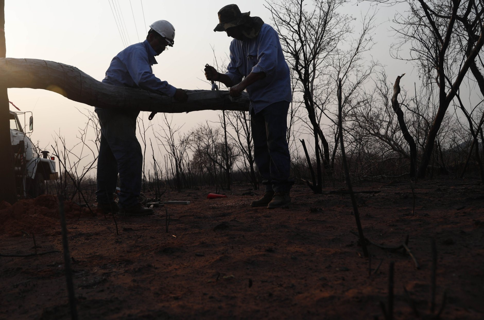 Electrical network workers repair an electric power pole, in the aftermath of a forest fire near the town of Robore, Bolivia, Friday, Aug. 23, 2019. Bolivia, along with Brazil, is struggling to contain wildfires, many believed to have been set by farmers clearing land for cultivation. (AP Photo/Juan Karita)