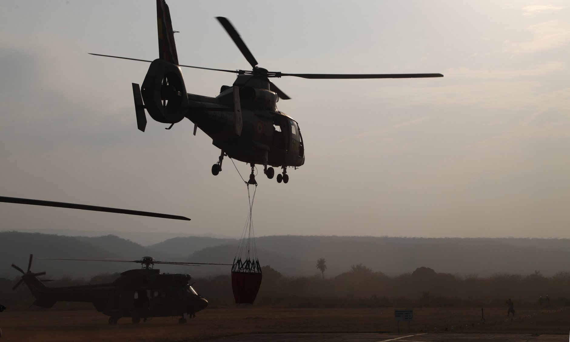 A helicopter lifts off from a military airport Robore, Bolivia, with water to drop on the Chiquitanía Forest as the military fights forest fires, Sunday, Aug. 25, 2019. Bolivian President Evo Morales said Saturday he would welcome aid in fighting his country's wildfires, which have scorched more than 2,900 square miles (744,000 hectares) of land in the Chiquitanía region over the past two weeks. (AP Photo/Juan Karita)