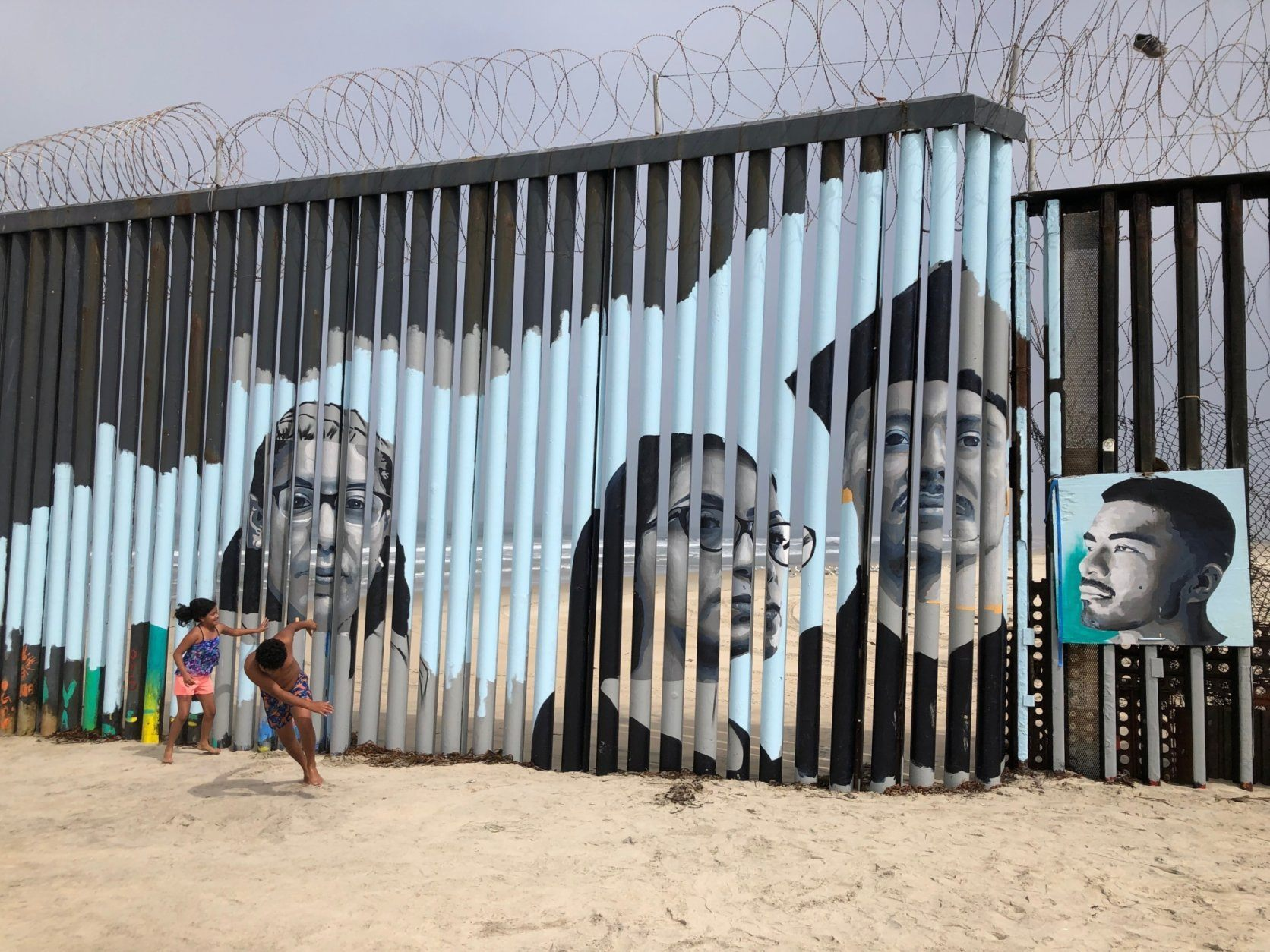 Children play in front of a new mural on the Mexican side of a border wall in Tijuana, Mexico Friday, Aug. 9, 2019. The mural shows faces of people deported from the U.S. with barcodes that activate first-person narratives on visitors' phones. Lizbeth De La Cruz Santana conceived the interactive mural in Tijuana as part of doctoral dissertation at the University of California, Davis. (AP Photo/Elliot Spagat)