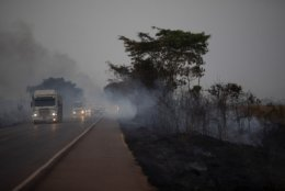 Trucks drive alongside scorched fields on the BR 163 highway in the Nova Santa Helena municipality, in the state of Mato Grosso, Brazil, Friday, Aug. 23, 2019. Under increasing international pressure to contain fires sweeping parts of the Amazon, Brazilian President Jair Bolsonaro on Friday authorized use of the military to battle the massive blazes. (AP Photo/Leo Correa)