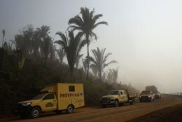 A line of fire fighting vehicles advance through smoke from forest fires in the Vila Nova Samuel region, along the road to the National Forest of Jacunda, near to the city of Porto Velho, Rondonia state, part of Brazil's Amazon, Sunday, Aug. 25, 2019. Leaders of the Group of Seven nations said Sunday they were preparing to help Brazil fight the fires burning across the Amazon rainforest and repair the damage even as tens of thousands of soldiers were being deployed to fight the blazes that have caused global alarm. (AP Photo/Eraldo Peres)