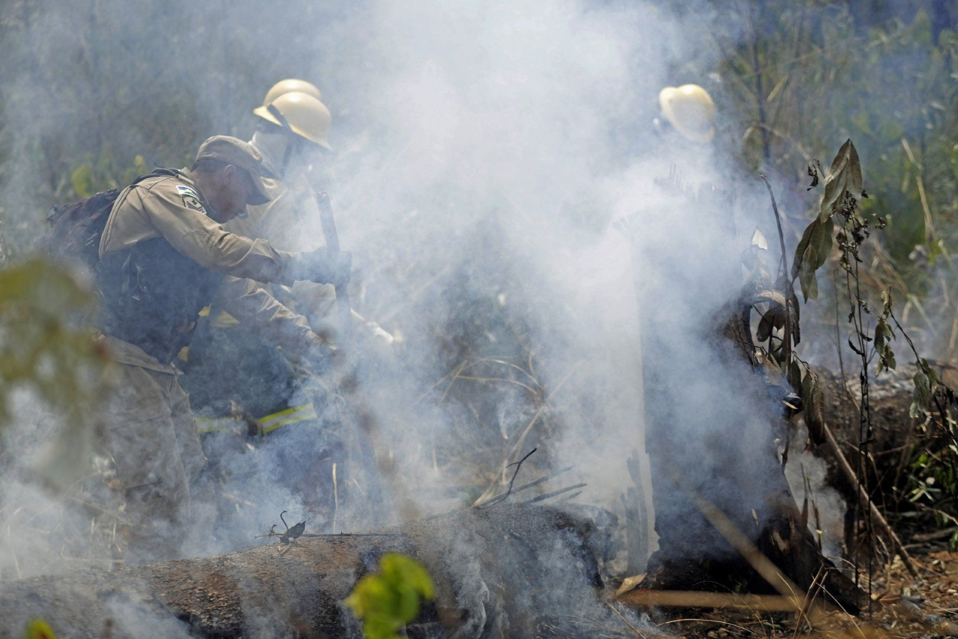 Firefighters work to put out forest fires along the road to Jacunda National Forest near the city of Porto Velho in Rondonia state, in the Vila Nova Samuel region, part of Brazil's Amazon, Sunday, Aug. 25, 2019. Leaders of the Group of Seven nations said Sunday they were preparing to help Brazil fight the fires burning across the Amazon rainforest and repair the damage even as tens of thousands of soldiers were being deployed to fight the blazes that have caused global alarm. (AP Photo/Eraldo Peres)