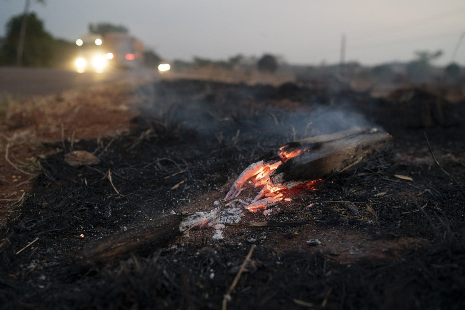 Embers from a wildfire smolder along BR 163 highway in the Nova Santa Helena municipality, in the state of Mato Grosso, Brazil, Friday, Aug. 23, 2019. Under increasing international pressure to contain fires sweeping parts of the Amazon, Brazilian President Jair Bolsonaro on Friday authorized use of the military to battle the massive blazes. (AP Photo/Leo Correa)