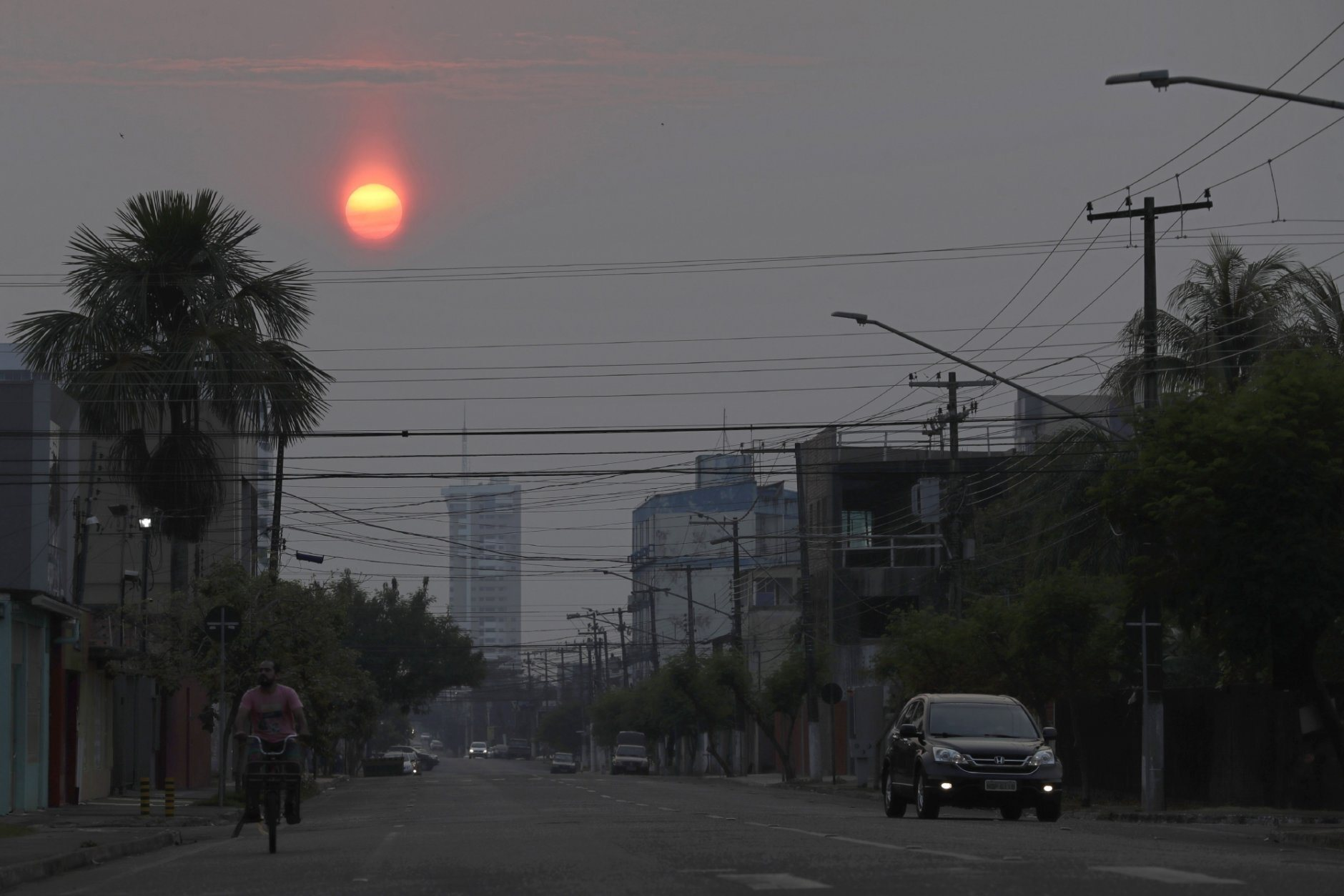 The sun, dimmed by the pall of smoke that cover the city, rises in the city of Porto Velho,  Rondonia state, Brazil, Saturday, Aug. 24, 2019. Brazil says military aircraft and 44,000 troops will be available to fight fires sweeping through parts of the Amazon region. The defense and environment ministers have outlined plans to battle the blazes that have prompted an international outcry as well as demonstrations in Brazil against President Jair Bolsonaro's handling of the environmental crisis. (AP Photo/Eraldo Peres)