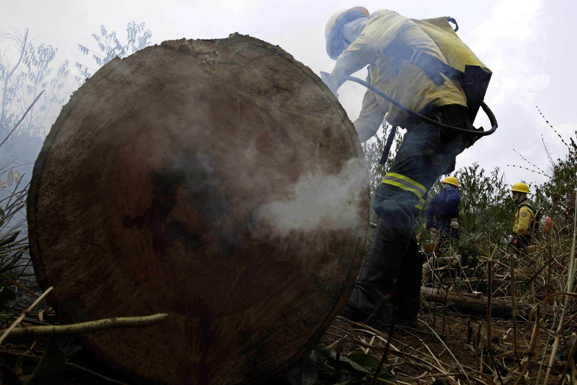 Firefighters work to put out flames in the Vila Nova Samuel region, along the road to the National Forest of Jacunda, near the city of Porto Velho, in Rondonia state, Brazil, Sunday, Aug. 25, 2019. Leaders of the Group of Seven nations said Sunday they were preparing to help Brazil fight the fires burning across the Amazon rainforest and repair the damage even as tens of thousands of soldiers were being deployed to fight the blazes that have caused global alarm. (AP Photo/Eraldo Peres)