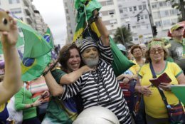 "A man wearing a prison costume and mask of Brazil's former President Luiz Inacio Lula da Silva poses for photos with anther person grasping his neck, during a rally in support of the government's ""Car Wash"" investigation into corruption on Copacabana beach, Rio de Janeiro, Brazil, Sunday, Aug. 25, 2019. Da Silvia is currently serving a prison sentence for corruption. (AP Photo/Silvia Izquierdo)"