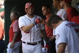 Washington Nationals' Matt Adams, front left, continues to celebrate his three-run home run in the dugout during the first inning of a baseball game against the Milwaukee Brewers, Sunday, Aug. 18, 2019, in Washington. (AP Photo/Nick Wass)