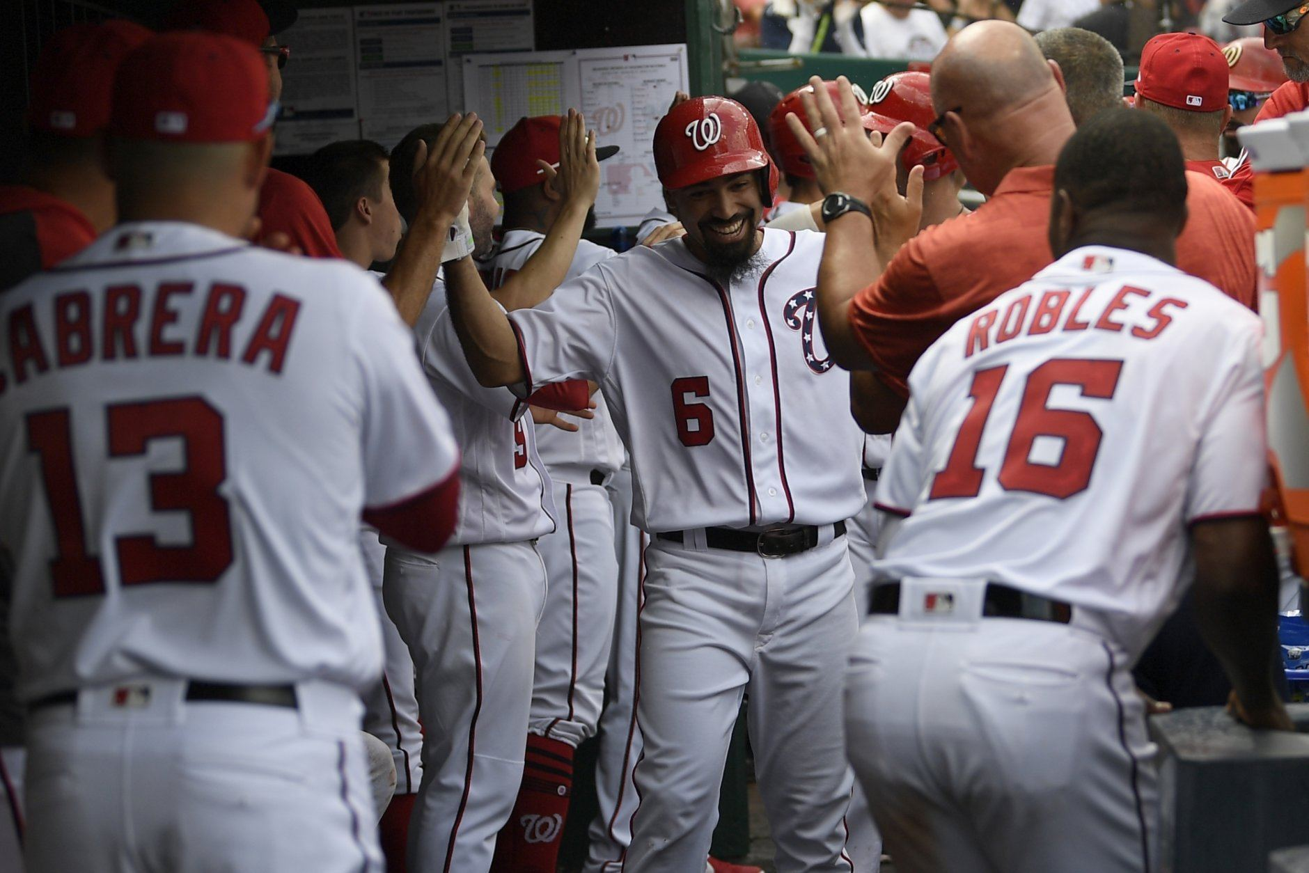 Washington Nationals' Anthony Rendon (6) celebrates his three-run home run in the dugout during the third inning of a baseball game against the Milwaukee Brewers, Sunday, Aug. 18, 2019, in Washington. (AP Photo/Nick Wass)