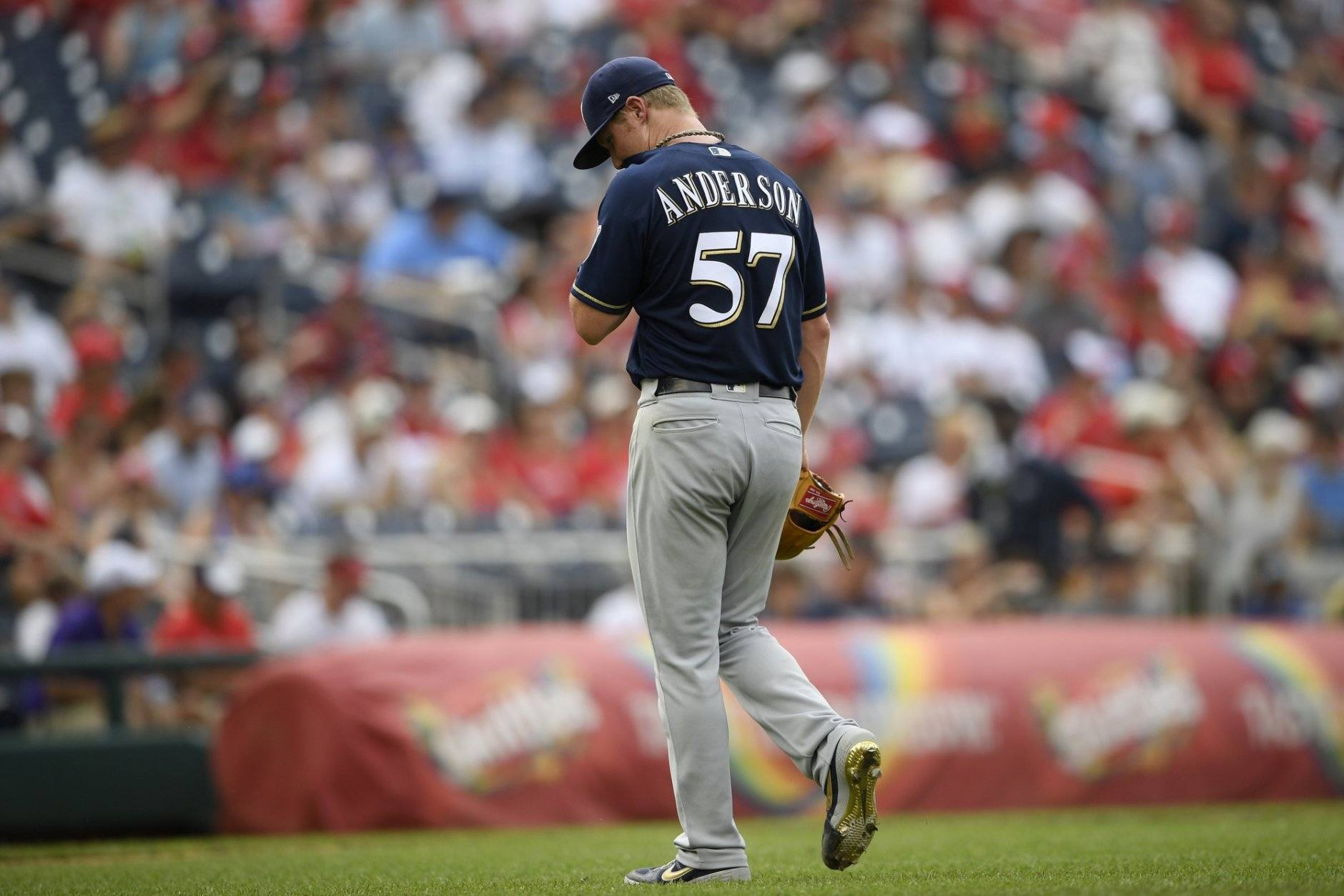 Milwaukee Brewers starting pitcher Chase Anderson walks toward the dugout after he was pulled during the third inning of a baseball game against the Washington Nationals, Sunday, Aug. 18, 2019, in Washington. (AP Photo/Nick Wass)