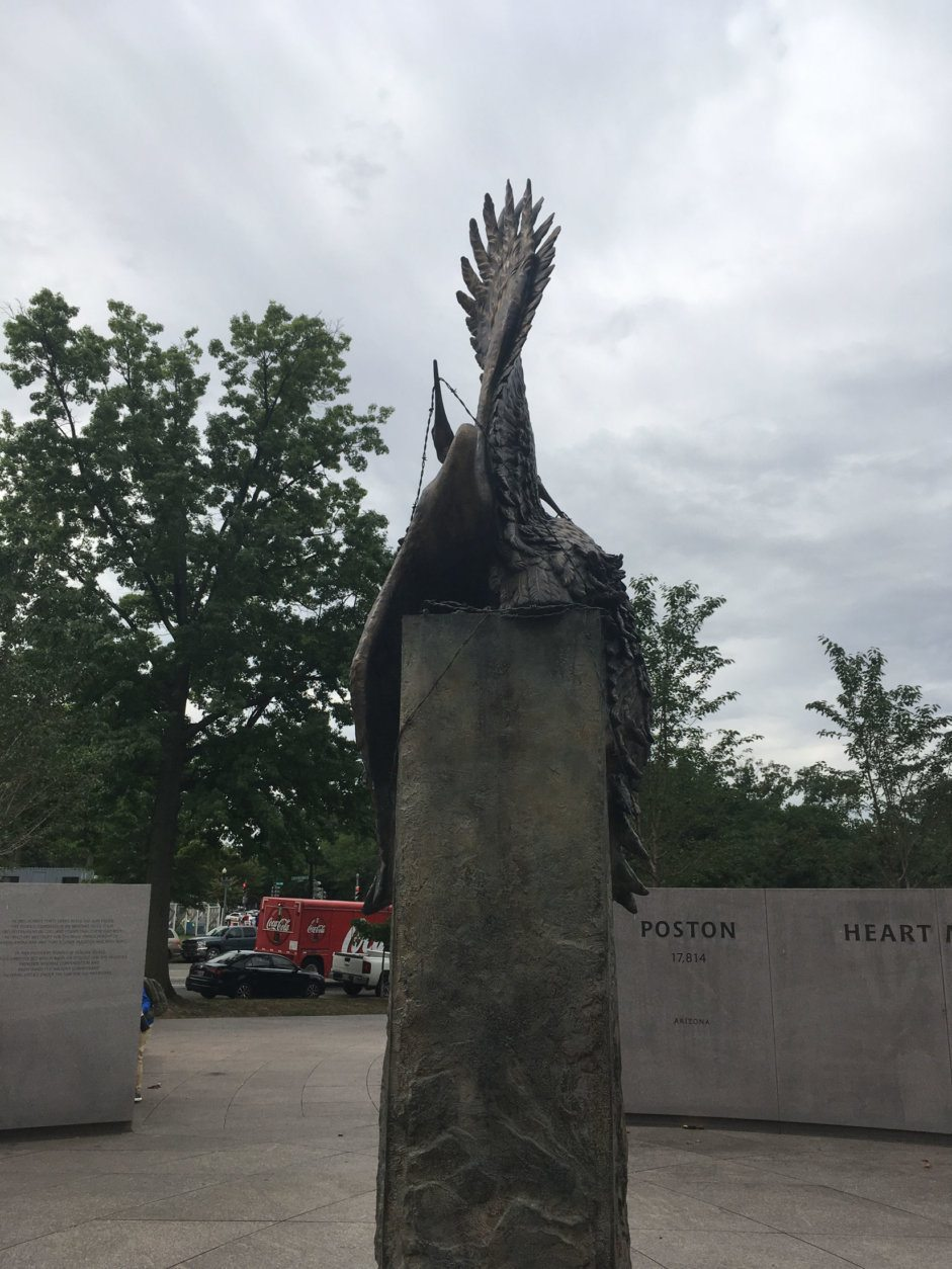 <p>In between the two areas of the memorial sits a sculpture by artist Nina Akamu that depicts two cranes entangled in barbed wire. But if you look at it from the back, Kelley said, the birds' wings take the shape of a torch — a symbol of freedom, as well as the symbol of the 442nd.</p>