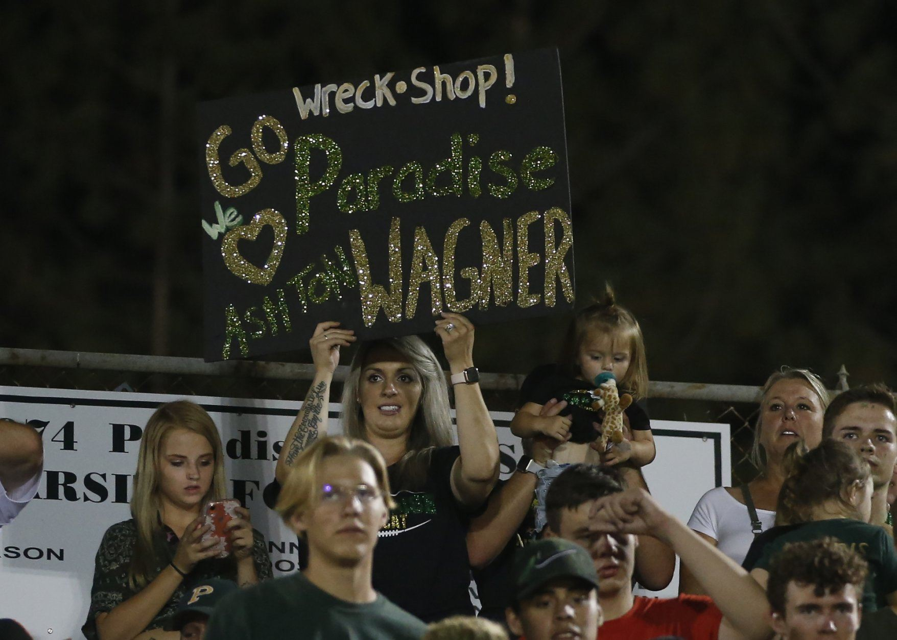 Paradise High School running back Ashton Wagner is shown support from people in the stands during the game against Williams High School in Paradise, Calif., Friday, Aug. 23, 2019. This was the first game for the school since a wildfire last year that killed dozens and destroyed nearly 19,000 buildings including the homes of most of the players. Paradise won 42-0. (AP Photo/Rich Pedroncelli)