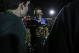 Paradise High School running back Lukas Hartley, center, talks with friends after defeating Williams High School 42-0 in Paradise, Calif., Friday, Aug. 23, 2019. This was the first game for the school since a wildfire last year that killed dozens and destroyed nearly 19,000 buildings including the homes of most of the players. (AP Photo/Rich Pedroncelli)