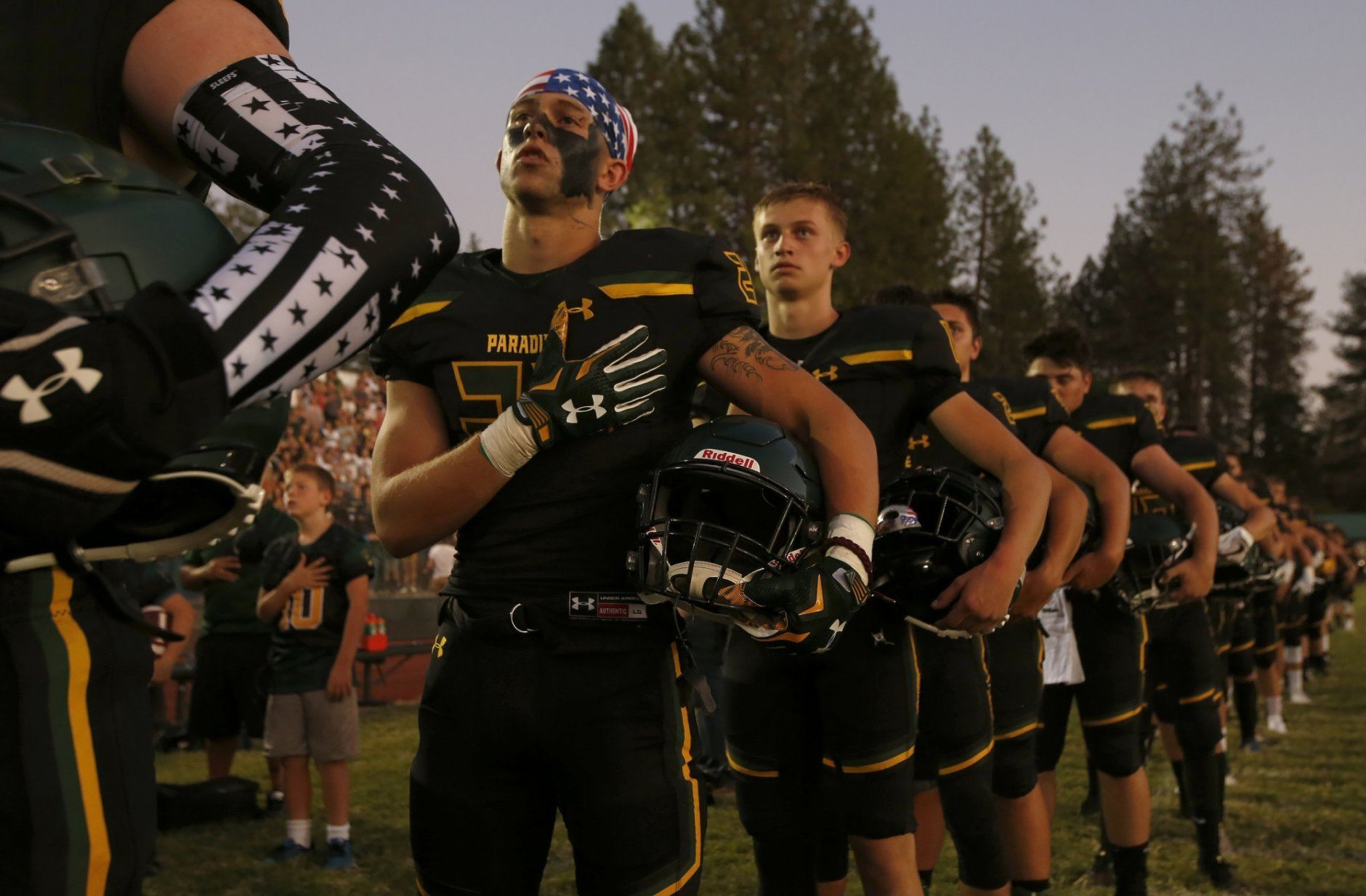Members of the Paradise High School football team stand for the playing of the national anthem before their game against Williams High School in Paradise, Calif., Friday, Aug. 23, 2019. This was the first game for the school since a wildfire last year that killed dozens and destroyed nearly 19,000 buildings including the homes of most of the players. Paradise won 42-0. (AP Photo/Rich Pedroncelli)