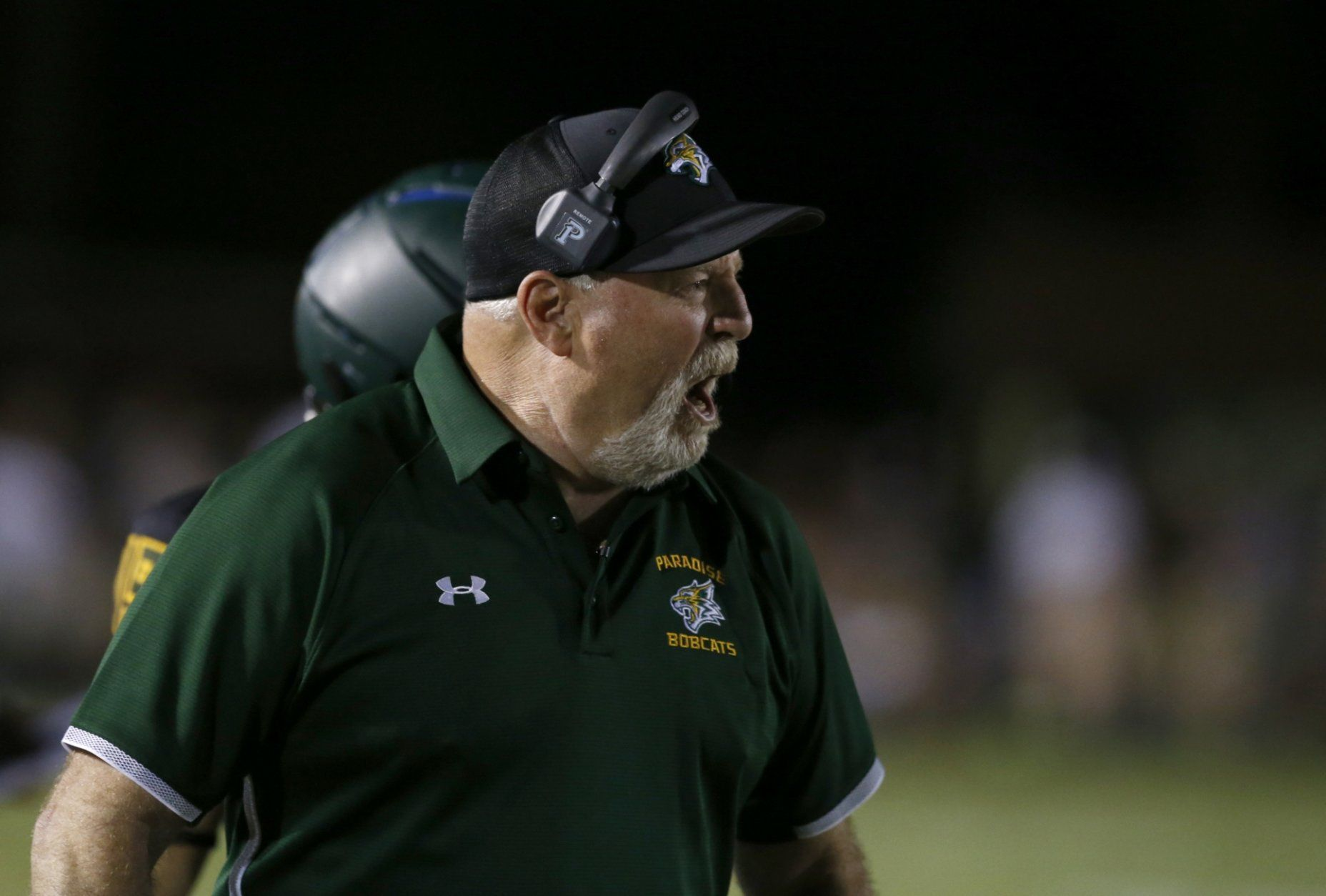 Paradise High School head football coach Rick Prinz calls out instructions to his team during the first half of their game against Williams High School in Paradise, Calif., Friday, Aug. 23, 2019. This was the first game for the school since a wildfire last year that killed dozens and destroyed nearly 19,000 buildings including the homes of most of the players. Paradise won 42-0. (AP Photo/Rich Pedroncelli)