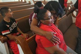 Shevona Overton, seated, gets a hug from her aunt Jennifer Overton during a news conference, Monday, Aug. 12, 2019, at Second Baptist Church, on E. 26th Street, in Erie, Pa. Shevona Overton lost her four children in a fatal fire a day earlier at a home child care center in Erie. A fifth child also died and at least two others were injured in the fire. (Christopher Millette/Erie Times-News via AP)